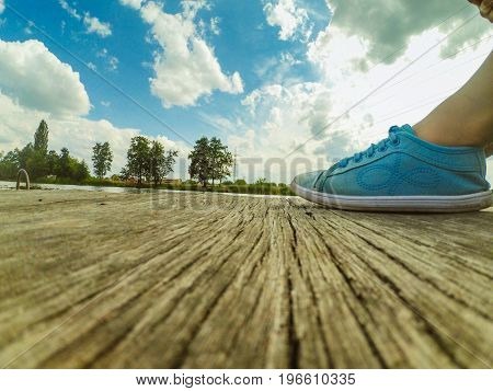 Legs in blue moccasins on a wooden dock Against the backdrop of a blue sky with white clouds