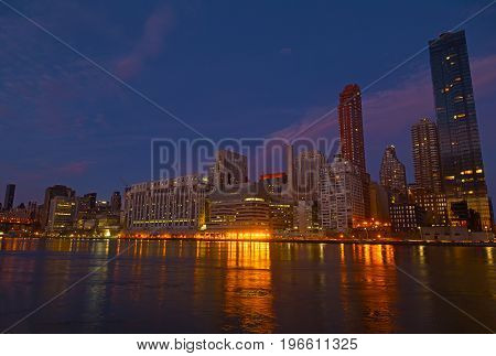 Manhattan panorama at dusk as seen from Roosevelt Island in New York USA. New York night scene with East River waterfront illuminated buildings.