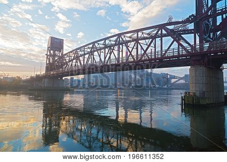 Roosevelt Island Bridge across the East Channel of the East River on foggy morning in New York USA. Urban infrastructure of metropolis with reflection in river waters.