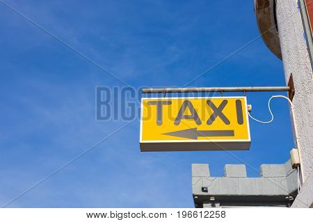Yellow Taxi Sign against the blue sky in the city