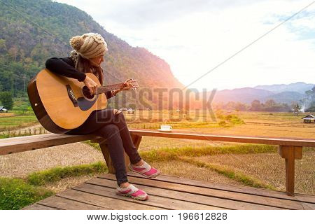 Women playing acoustic guitar in the rice field ralax and lifestyle. Travel Concept