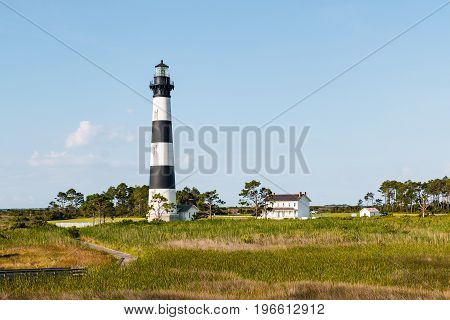 A wooden boardwalk trail through marshland leading to the Bodie Island lighthouse and adjacent buildings on the Outer Banks of North Carolina.