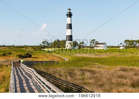 NAGS HEAD, NORTH CAROLINA - JULY 14, 2017:  On the Outer Banks, visitors to the Bodie Island lighthouse walk on the wooden ramp which is elevated above the surrounding marshland.