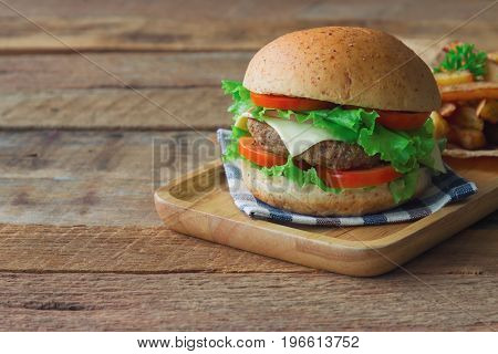 Homemade hamburger on plaid napkin with french fries. Delicious sandwich hamburger with meat or pork ham cheese and fresh vegetable. Hamburger or sandwich is the popular fast food for brunch or lunch.Homemade burger sandwich ready to served