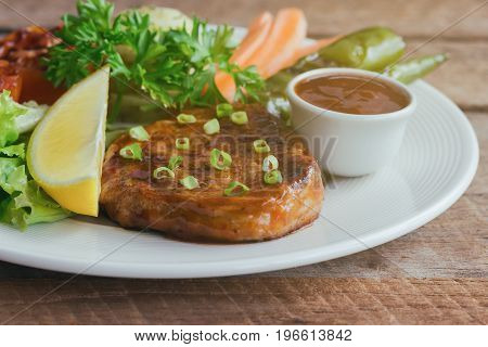 Barbecue pork steak on white plate served with barbecue sauce and vegetables. Pork steak for lunch or dinner on wood table. Moist and soft homemade pork barbecue with mash potato and vegetable. Homemade barbecue pork steak ready to served.