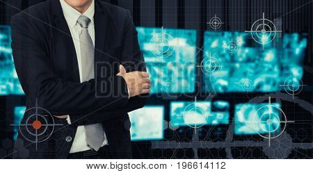 Male model in a suit posing on security system while looking at CCTV footage.