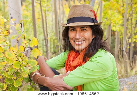 Hispanic woman sitting in forest