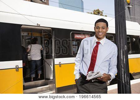 Businessman reading newspaper on city street