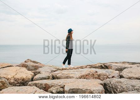 A traveler in a hat walks by the sea. Travel, tourism.