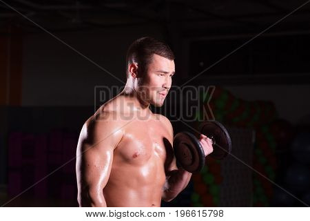 Athletic shirtless young male fitness model holds the dumbbells
