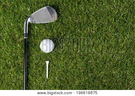 Golf ball with wooden tee and putter lies against the background of grass