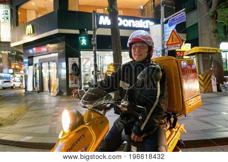 SEOUL, SOUTH KOREA - CIRCA MAY, 2017: man drive McDonald's delivery motorbike in Seoul. McDonald's is an American hamburger and fast food restaurant chain.