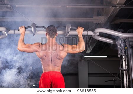 Strong man doing pull-ups on a bar in a gym