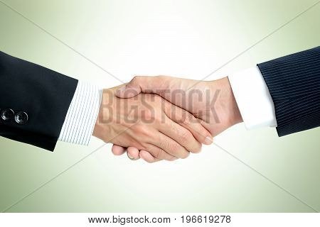 Handshake of businessmen in light green background - greeting dealing merger & acquisition concepts
