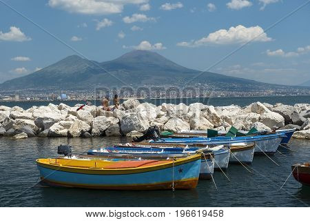 Naples, Italy - may 18, 2017: fishing boats in the port of Naples and view of Mount Vesuvius and Gulf of Naples in good weather, Naples, Italy