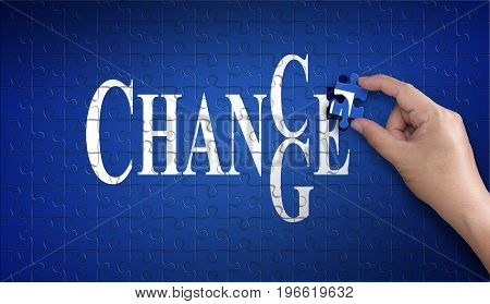 chanse to change word on Jigsaw puzzle - business concept. Man hand holding a blue puzzle to complete the word chanse to change divided over them concept of the solution to a problem challenge plan and strategy.