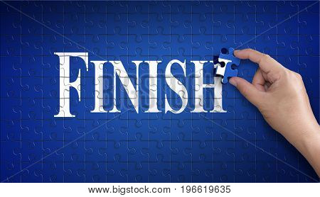 Finish word on Jigsaw puzzle - business concept. Man hand holding a blue puzzle to complete the word Finish divided over them concept of the solution to a problem challenge plan and strategy.