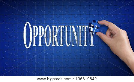 Opportunity word on Jigsaw puzzle - business concept. Man hand holding a blue puzzle to complete the Opportunity Finish divided over them concept of the solution to a problem challenge plan and strategy.