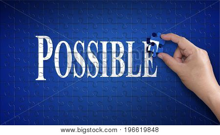 Possible word on Jigsaw puzzle - business concept. Man hand holding a blue puzzle to complete the word Possible divided over them concept of the solution to a problem challenge plan and strategy.