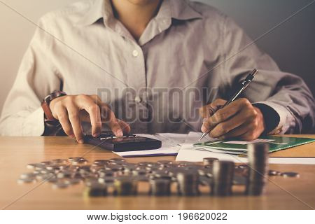 hand holding a pen and calculator on the table with a medal recognizing computation and Sunset light Business Background.