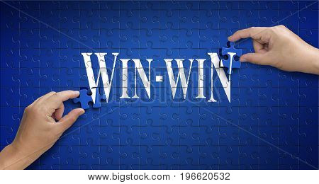 win win word on Jigsaw puzzle - business concept. Man hand holding a blue puzzle to complete the word win-win divided over them concept of the solution to a problem challenge plan and strategy.
