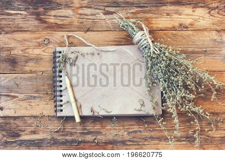Bunch of dry herb wormwood notepad for writing pencil on a wooden table rustic style
