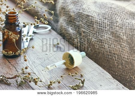 Bundle of dried herbs absinthe bottle of oil and pipette scissors on wooden table burlap rustic style