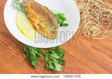 Fragment of the white dish with fried crucian slices of the lemon twigs od the parsley and dill and part of the fishing net on a surface of the old wooden planks