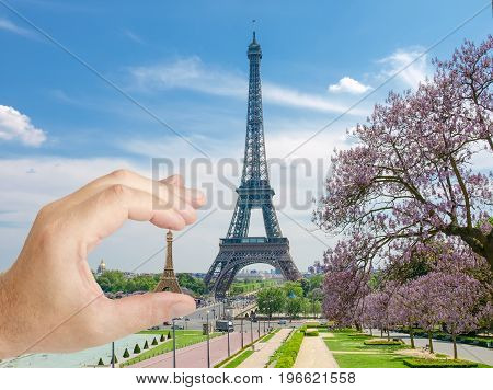 Eiffel Tower with with blossoming trees and small metal Eiffel Tower model in man's hand in a foreground in Paris
