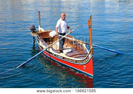 VITTORIOSA, MALTA - MARCH 31, 2017 - Man steering a traditional Maltese Dghajsa water taxi in the harbour Vittoriosa Malta Europe, March 31, 2017.