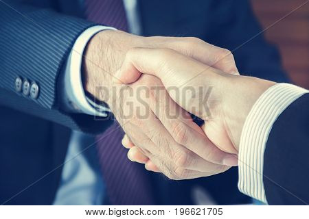 Handshake of businessmen in vintage tone - greeting dealing merger and acquisition concepts