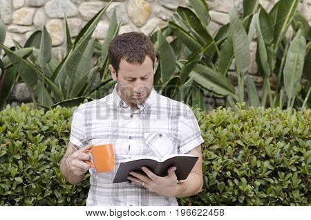 Young man in a plaid shirt reading a leather bound book outdoors while holding an orange coffee mug.
