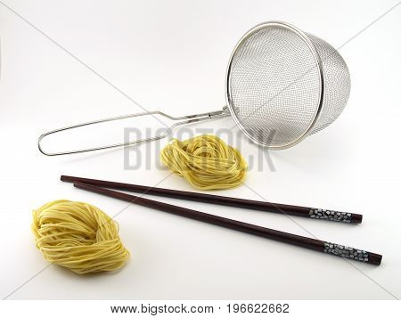 two yellow noodles with brown wooden chopsticks and silver metallic colander isolated on white background, prepare to boil noodles, Chinese food
