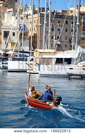 VITTORIOSA, MALTA - MARCH 31, 2017 - Passengers on board a traditional Maltese Dghajsa water taxi in the harbour with views towards Senglea waterfront Vittoriosa Malta Europe, March 31, 2017.
