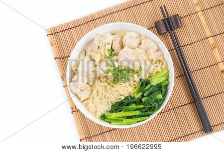 Wonton and egg noodle soup of Chinese Cantonese style for asian cuisine serving with Chinese cabbage (bog choy) and topped over bamboo plate mat isolated on white background flat lay (top view)