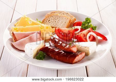 Breakfast - fried sausages, yellow cheese and vegetables