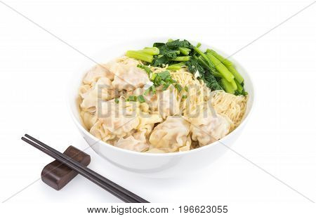 Wonton and egg noodle soup of Chinese Cantonese style for asian cuisine serving with Chinese cabbage (bog choy) and topped with chopped green onion over bamboo plate mat isolated on white background