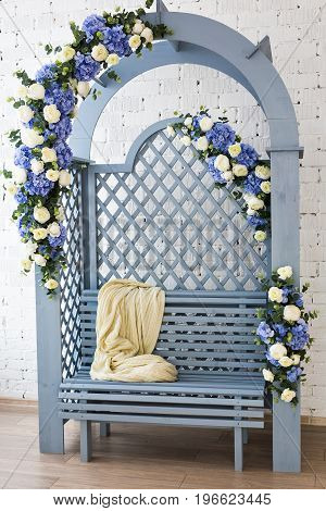 Cozy soft plaid on blue wooden bench.