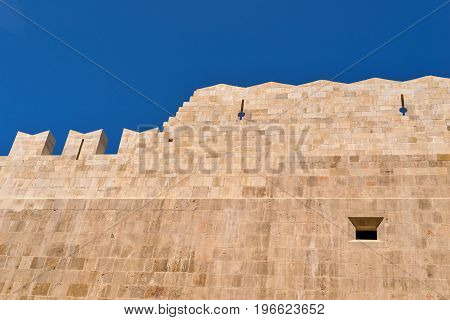 big stone wall of ancient fortress against the background of the clear and clear sky