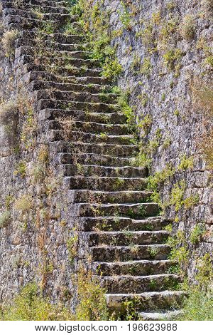 old stone ladder on an ancient stone wall of fortress closeup