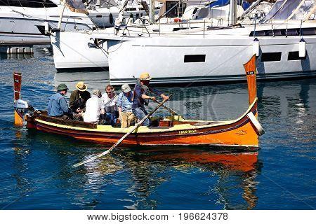 VITTORIOSA, MALTA - MARCH 31, 2017 - Passengers on board a traditional Maltese Dghajsa water taxi in the harbour Vittoriosa Malta Europe, March 31, 2017.