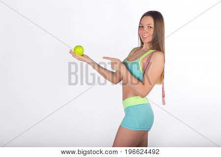 Fitness woman points finger at apple measuring tape on the shoulder white background side view. Vitamin care health food. Healthy lifestyle