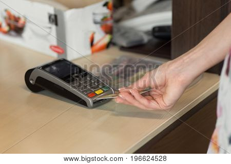 Female customer paying by credit card in cafe. Focus on woman hands entering security pin in credit card reader.