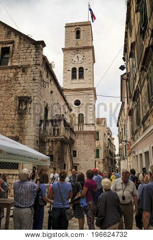 SIBENIK CROATIA - SEPTEMBER 9 2016: Tourists are visiting the sights in the old Croatian town near the church of St. John.