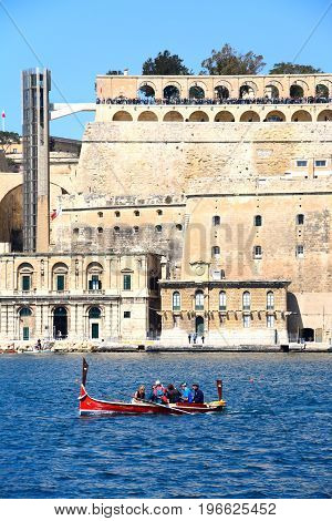 VALLETTA, MALTA - MARCH 31, 2017 - Passengers on board a traditional Maltese Dghajsa water taxi in the grand harbour with views towards Upper Barrakka Gardens Valletta Malta Europe, March 31, 2017.