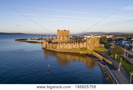 Medieval Norman Castle in Carrickfergus near Belfast, Northern Ireland, UK. Aerial view at sunrise with far view of Belfast in the background.
