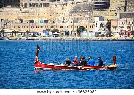 VALLETTA, MALTA - MARCH 31, 2017 - Passengers on board a traditional Maltese Dghajsa water taxi in the grand harbour with views towards Valletta waterfront buildings Valletta Malta Europe, March 31, 2017.