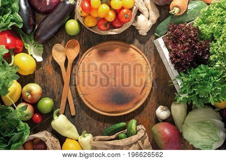 Around the round kitchen board set of fresh vegetables and fruits on a wooden table top view. Food background