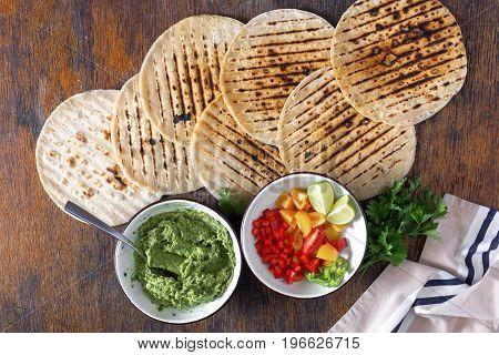 Vegetarian tortillas on wooden table. Ingredients for cooking vegetarian tortillas top view