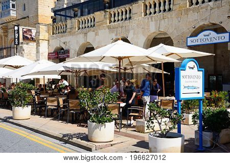 VITTORIOSA, MALTA - MARCH 31, 2017 - Tourists relaxing at the Sottovento pavement cafe along the waterfront Vittoriosa Malta Europe, March 31, 2017.